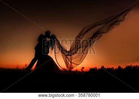 Silhouette Of Bride And Groom Kissing At Sunset. The Veil Is Flying.