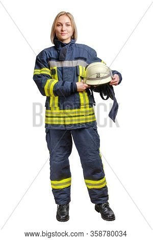 Young Smilng Firefighter Woman In Fireproof Uniform Stands And Looks At The Camera With A Helmet In