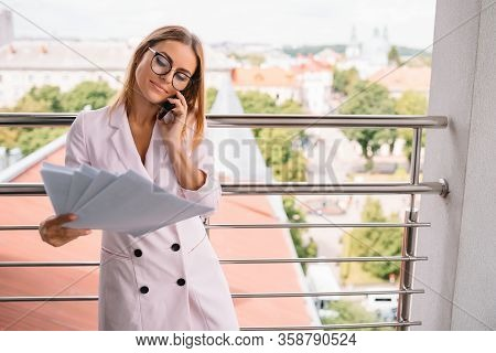 Business Woman On The Phone At Office. Young Business Woman Having Phone Call At The Office. Smiling