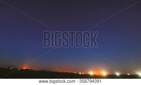 Night Starry Sky With Glowing Stars Above Landscape With Town City Lights. Night Starry Sky Above Gr