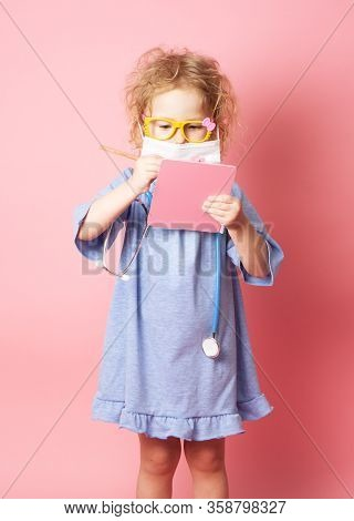 Pediatrics: A Little Girl In The Form Of A Nurse With Glasses And With A Stethoscope Fills A Prescri