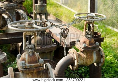 Chain With A Lock On The Valves Of Water Pipes. Protection Against Unauthorized Access.