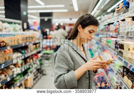 Young Woman Shopping In The Supermarket Grocery Store.reading Ingredients,declaration Or Expiration