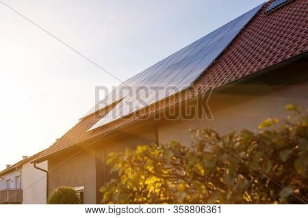 Solar Panels On The Tiled Roof Of The Building In The Sun Set.