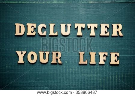 Declutter your life text on a wood table.