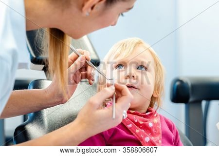 Dentist explaining treatment to a child using a plush toy, the little girl is watching