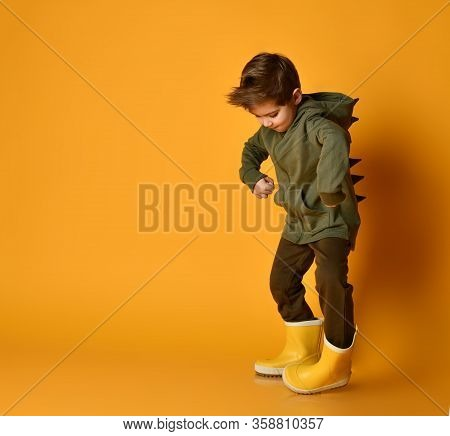 Little Brunet Kid In Khaki Dino Hoodie With Hood And Pants, Yellow Rubber Boots. He Is Posing Agains