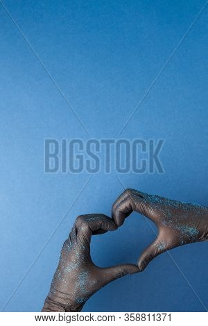 The Heart, Figure Built From The Hands In Balck Rubber Medical Gloves With Glitter On A Blue Backgro