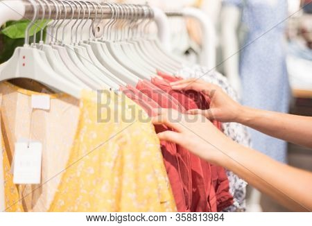 Female Hand Choosing Clothes For Checked Pattern Cotton Dress On The Rack In Cloth Shop At Cloth Sho