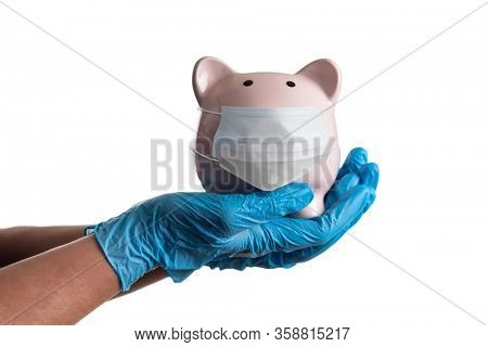 Doctor or Nurse Wearing Surgical Gloves Holding Piggy Bank Wearing Medical Face Mask Isolated on White.