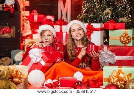 Small Kids Relax Under Duvet White Drinking Milk. Santa Helpers Among Red Present Boxes. Too Much Gi