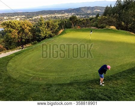 Victoria, British Columbia, Canada - August 19th, 2019: A Father And Son On A Putting Green Playing