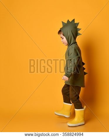 Little Brunet Kid In Khaki Dino Hoodie With Hood And Pants, Yellow Rubber Boots. He Is Walking Along
