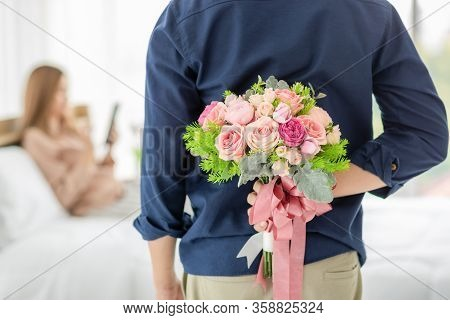Man Hiding Buch Of Colorful Flower At Back Prepare To Give For Woman Who Sitting On Bed And Playing