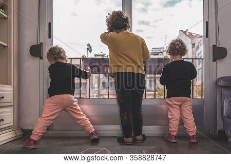 A Boy And His Two Twin Sisters Leaning Against The Window Saddened That They Cannot Go Out To The Pa