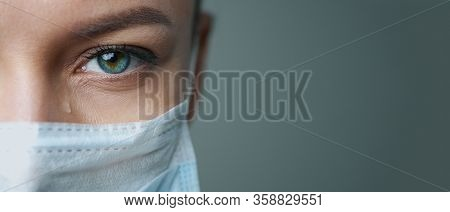 A Female Doctor Therapist In A White Robe, Mask And Gloves. Face Close-up. The Doctor Cries And Pray