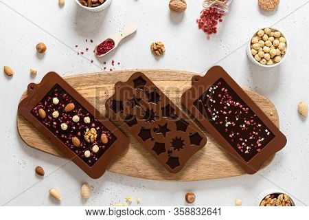 Homemade Chocolate Bars With Nuts And Dried Fruits In Molds. Chocolatier, Confectionery. Top View