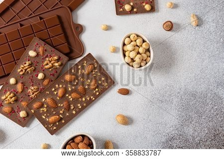 Homemade Milk Chocolate Bars And Molds. Chocolate Bars, Nuts, Dried Fruits On Gray Background Top Vi