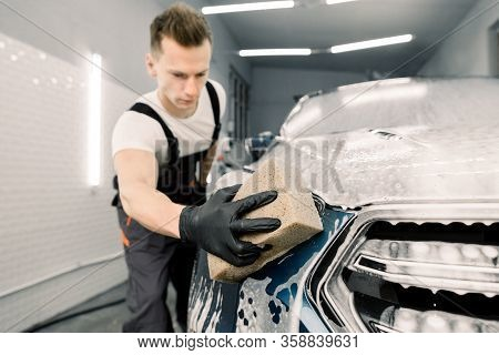 Young Man Car Wash Worker Washing A Soapy Dark Blue Car, Holding Sponge. Focus On The Hand In Black