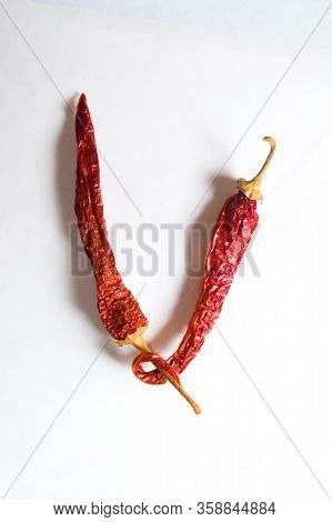 Letter V Lined With Red Peppers On A White Background. Symbol In The Form Of The Letter V. Pepper Li