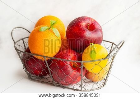 A Basket Of Fruits. A Set Of Vitamins. A Metal Basket With Apples And Oranges. Vitamin C. Lemon. Veg