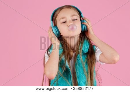 A Little Girl With Headphones Explodes Pink Chewing Gum On A Pink Background.