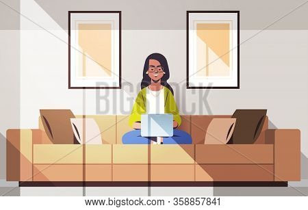Beautiful Indian Woman Sitting On Couch Using Laptop Girl Working From Home Freelance Concept Modern