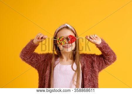 Little Girl Enjoy Lollipops During School Break. Happy Small Schoolchild Eat Lollipops. Large Swirl