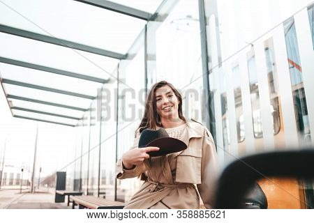 Girl In Stylish Clothes Sits At A Bus Stop And Is About To Throw Her Hat Up