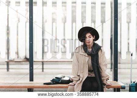 Young Traveler Lady In Coat And Hat With A Sad Face Sits At A Bus City Stop Alone