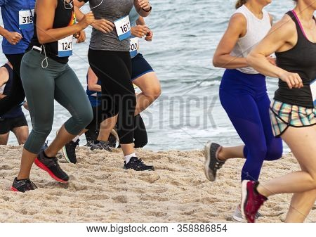Side View Of Runners Running A Race On A Beach By The Ocean As Part Of The New York State Parks Summ