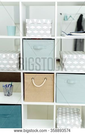 Boxes And Organizers In A White Office Cabinet. Bright Office In Blue And Beige Tones.