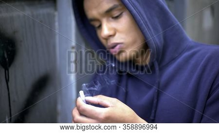 Thoughtful Teenager Smoking Nervously, Planning His Future, Cruel Reality