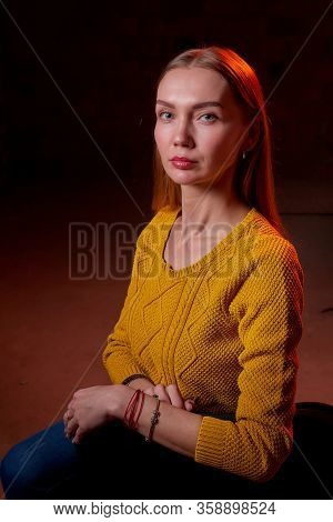 Portrait Of Elegant Woman With Long Hair In Yellow Sweater And Dark Background. Model Posing Doring