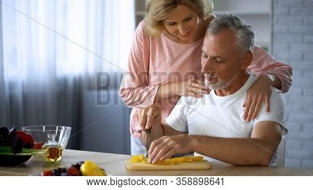 Handsome Man Cutting Fresh Vegetables, Caring Wife Hugging Him, Spouse Support