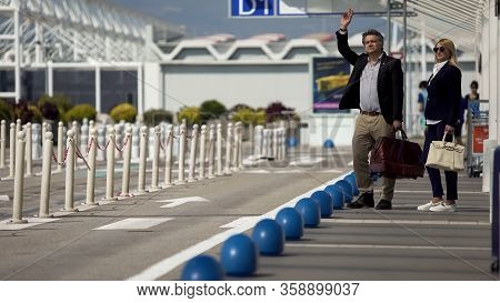 Business Trip, Man And Woman Hailing Taxi Near Airport, Transportation Services