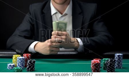 Businessman Gambler Contemplating Betting All Money On Poker Game At Casino