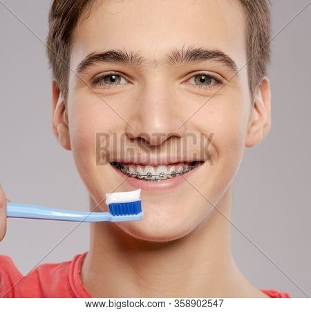 Photo of  young man taking care of his teeth. Dental hygiene. Teenager brushes his teeth with a toothbrush. Caucasian guy takes care of clean teeth with braces.  Person with healthy teeth.