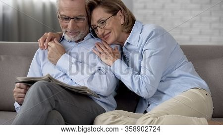 Happy Retiree Couple Sitting On Couch, Man Reading Newspaper, Lady Hugging Him