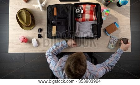 Man Carefully Packing Suitcase For Travel, Taking Money And Documents, Top View