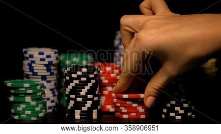 Hand Choosing Red Chip Among Stacks Of Tokens, Casino Game Odds, Lucky Bet