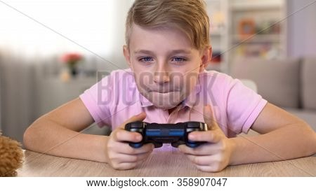 Excited Male Kid Playing Video Game With Console, Eyesight Problems Risk