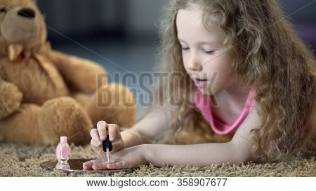 Concentrated Girl Painting Nails With Mothers Polish, Pretending To Be Older