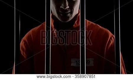 Mad Serial Killer Standing Behind Prison Bars And Smirking, Mental Disorder