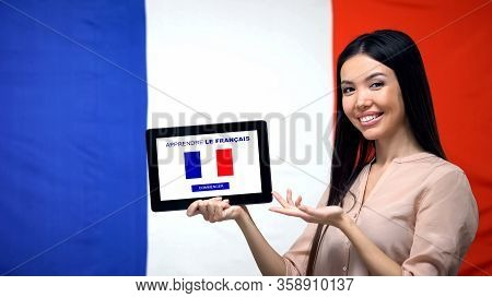 Lady Holding Tablet With Learn French App, France Flag On Background, Education