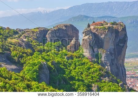 Holy Trinity Monastery On Cliff Rock Top, Meteora, Greece And Kalampaka Town In The Valley