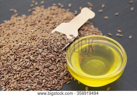 A Pile Of Flax Seeds And Flax Oil In A Wooden Spoon On A Black Stone Background. Dark Background Fla