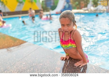 Happy Cheerful Little Girl In Colored Swimwear Emerges From The Pool On A Warm Sunny Summer Day. Con