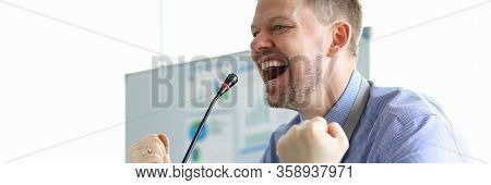 Male Speaker Clenched His Fists Front Microphone. Business Coach Is Working On Developing Practical