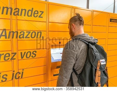 Man Using Amazon Locker In Shopping Mall, Orange Pick Up Point For Mail Order Goods With Amazon Bran